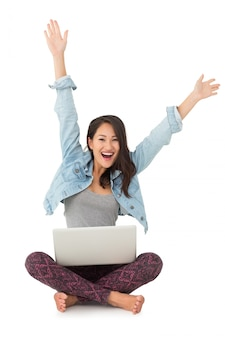 Asian woman cheering at camera with laptop sitting on floor
