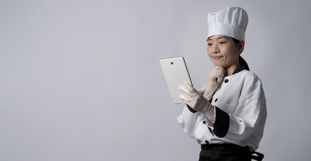 Asian woman chef holding smartphone or digital tablet and received food order from online shop