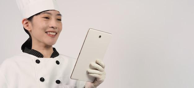 Азиатская женщина-повар держит смартфон или цифровой планшет и получает заказ на еду из интернет-магазина или приложения продавца. она улыбается в униформе шеф-повара и стоит в студии с белой стеной.