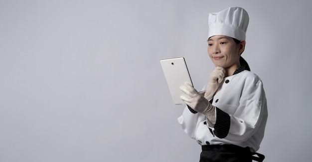 Азиатская женщина-повар держит смартфон или цифровой планшет и получает заказ на еду из интернет-магазина