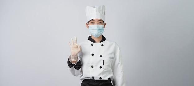 Азиатская женщина-шеф-повар в униформе белого цвета с гигиеническими средствами, такими как медицинская маска для лица и резиновая рука