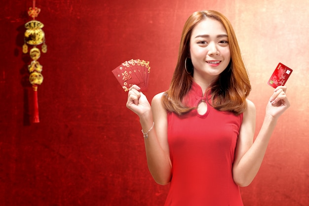Asian woman in a cheongsam dress holding a credit card and red envelopes
