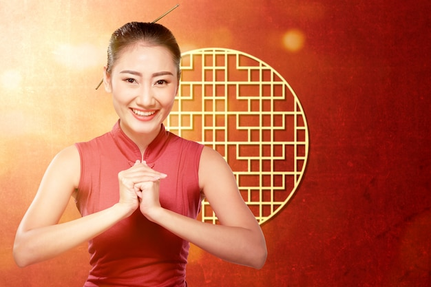 Asian woman in a cheongsam dress with congratulations gesture