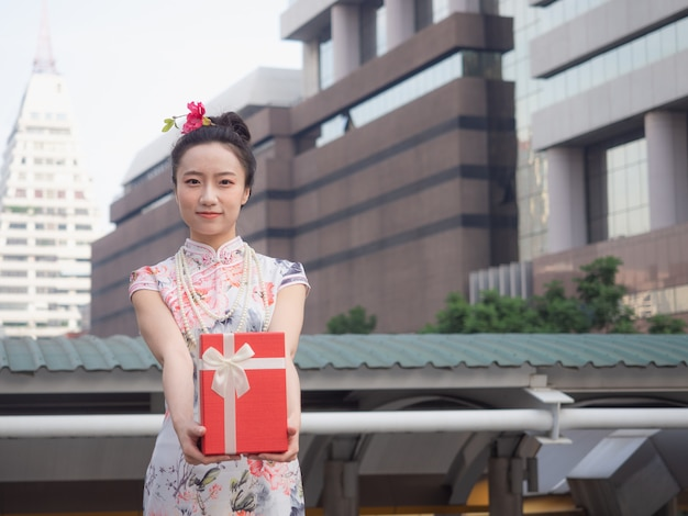 Asian woman in chinese dress holding red gift box in hand with city background