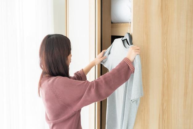 Азиатская женщина, выбирая одежду в комнате