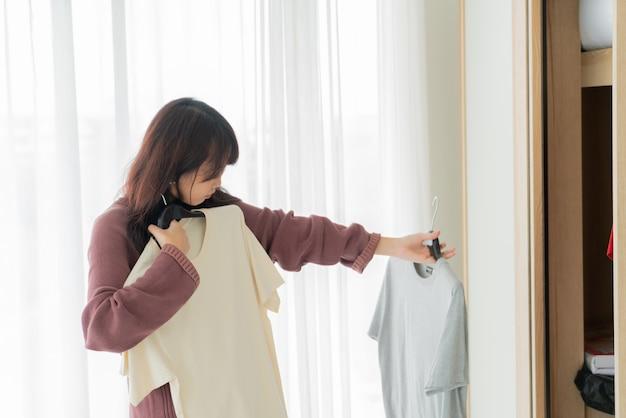 Asian woman choosing cloths in a room