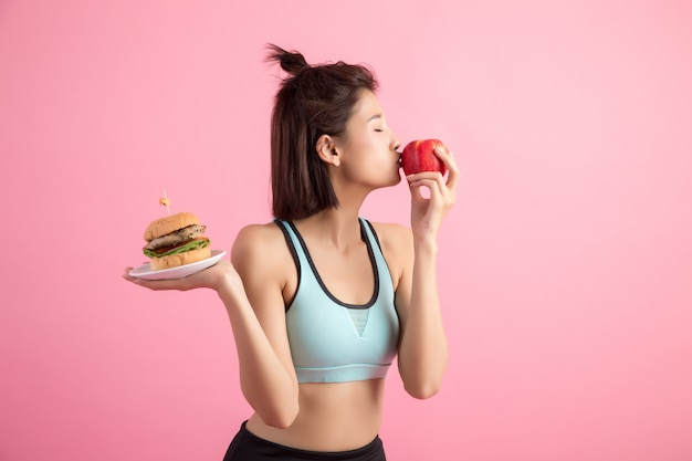 Asian woman choosing between hamburger and red apple on pink