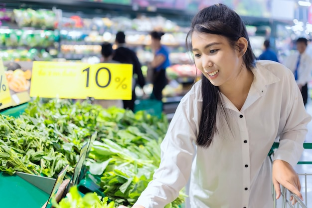 アジアの女性のスーパーマーケットでショッピングカートと店の野菜を選択します。スーパーマーケットのコンセプトでショッピング。