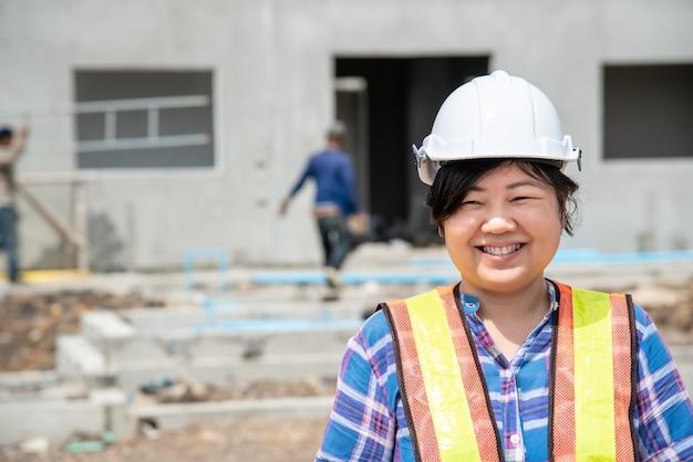 Азиатская женщина инженер-строитель или архитектор со шлемом и жилетом безопасности счастлива работать на здании или строительной площадке