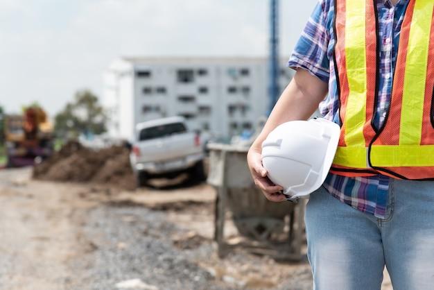建物や建設現場で幸せに働くヘルメットと安全ベストを持つアジアの女性土木エンジニアの労働者または建築家