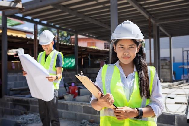 건설 현장에서 흰색 안전 헬멧을 입고 아시아 여자 토목 기사 종이 계획 건물 건축가.