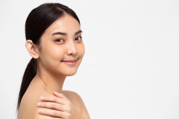 アジアの女性は白で隔離される健康な完璧な肌をオフにします。