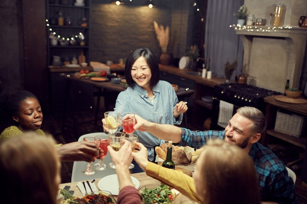 Asian woman clinking glasses with friends