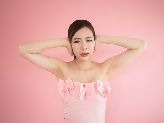 Asian woman close ears and feeling fear on pink background