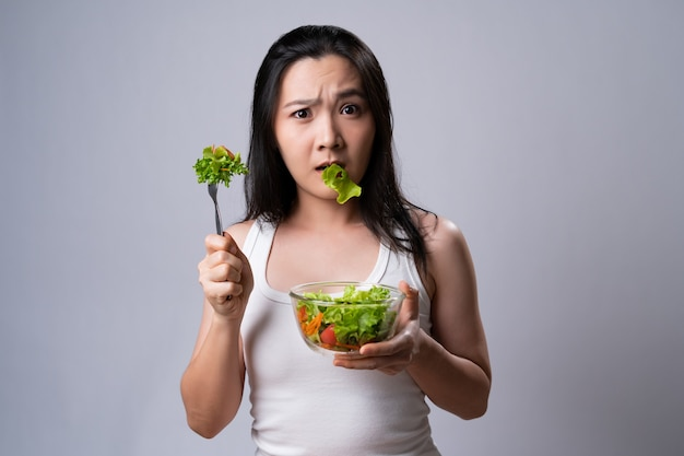 Asian woman confused with eating salad isolated over white wall. healthy lifestyle with clean food concept.