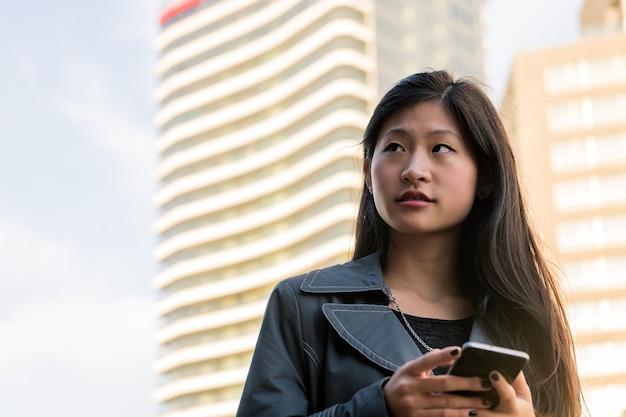 Азиатская женщина консультируется по телефону в центре города