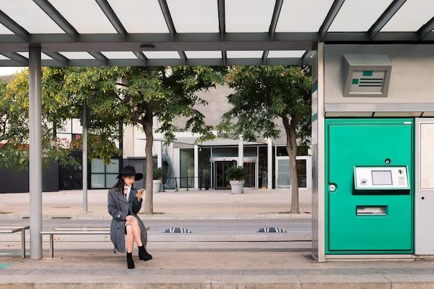 Азиатская женщина консультируется по телефону в ожидании автобуса