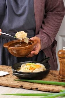아시아 여성 요리사 만두 전골 또는 완탕 수프, 다진 봄 양파를 곁들인 한국 및 중국 전통 만두 스튜