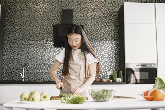 Donna asiatica che cucina a casa.