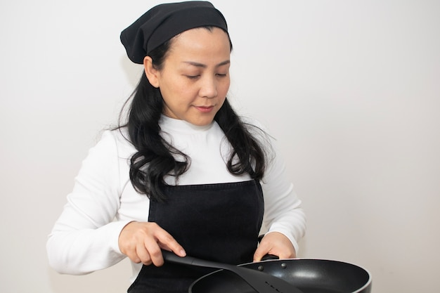 Asian woman in cooking suite carries black sauce pan