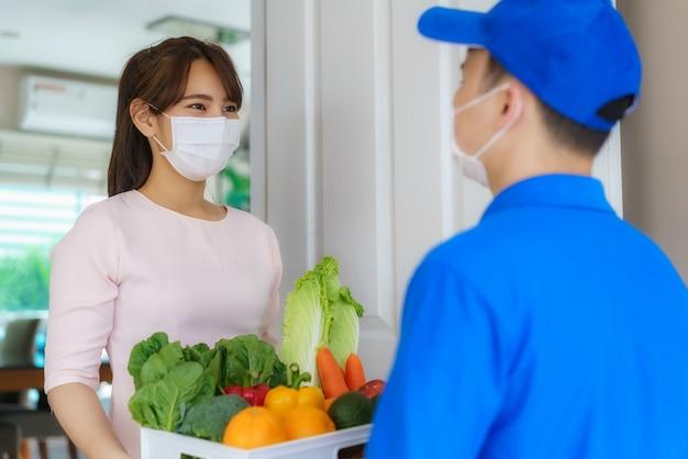 Азиатская женщина-покупатель в маске и перчатке получает коробку с продуктами, фруктами, овощами и напитками от доставщика перед домом во время домашней изоляции.