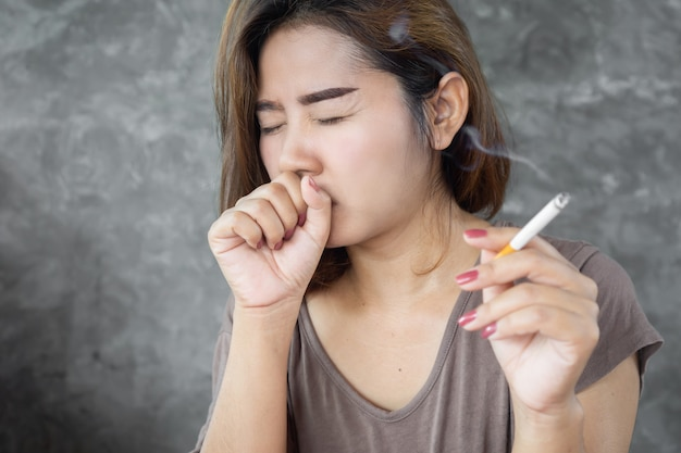 Asian woman coughing from smoking cigarette