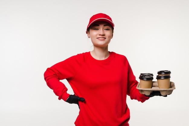 白で配達のためにコーヒーを保持しているアジアの女性宅配便