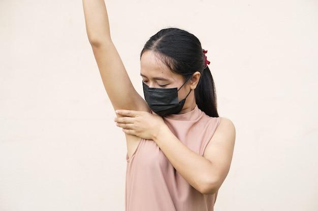 Азиатская женщина, охватывающая подмышки руками