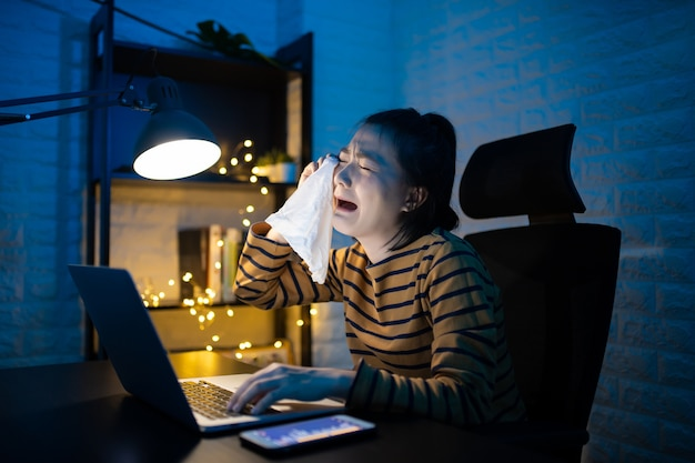 泣いて、自宅で残業しているティッシュペーパーを使用しているアジアの女性。 。コロナウイルスcovid19の概念を回避するために、自宅で仕事をします。