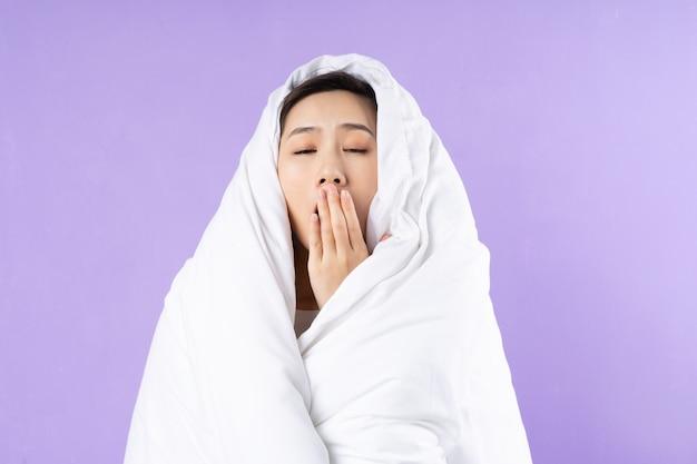 アジアの女性は紫色の背景に毛布で丸くなった