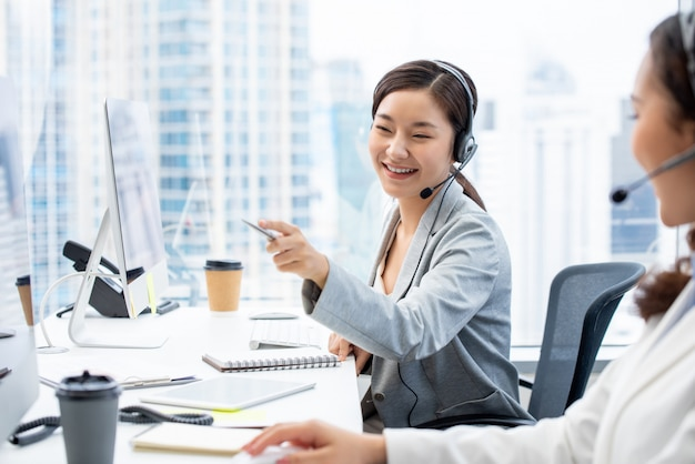 Asian woman customer service agent working in call center office