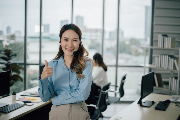 Asian woman customer support operator or call center with headset looking at front and smiling