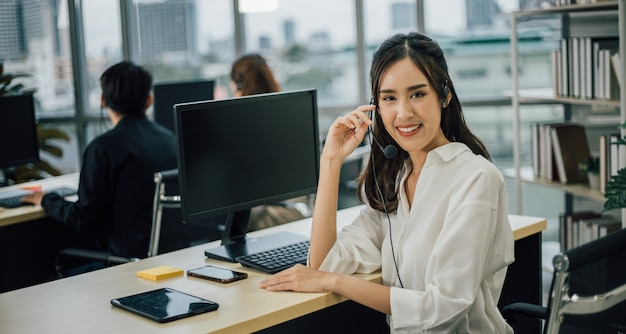 Asian woman customer support operator or call center with headset looking at front and smiling.