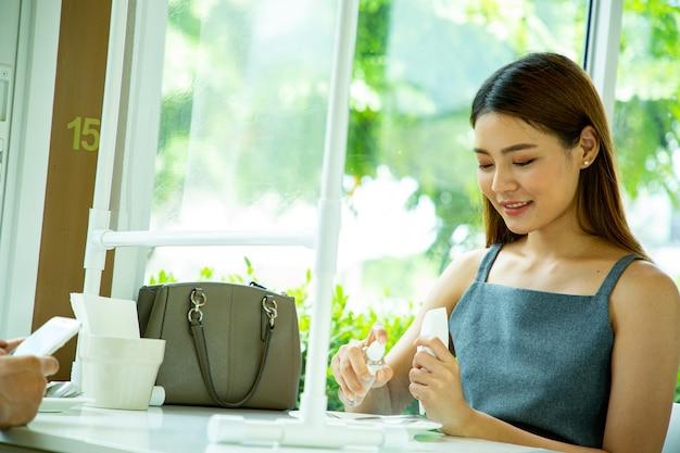 레스토랑에서 사용하기 전에 위생 접시와 도구를 위해 알코올 스프레이를 사용하는 아시아 여성 고객. 코로나 바이러스로부터의 예방. 비접촉 개념.