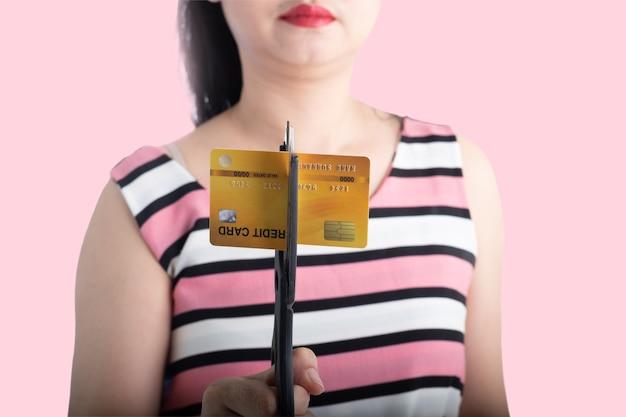 쇼핑에 대한 지출을 중단하기 위해 가위로 신용 카드를 자르는 아시아 여성