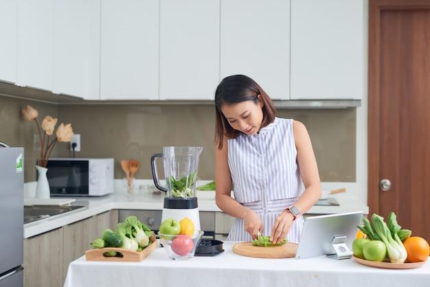 彼女の前にタブレットとキッチンで野菜を切るアジアの女性