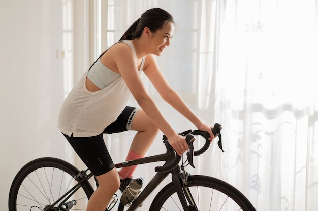 アジアの女性サイクリスト。彼女は家で運動しています。彼女はトレーナーでサイクリング