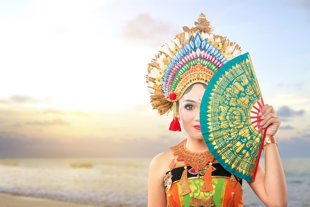 Asian woman dancing balinese traditional dance (kembang girang dance) on the beach
