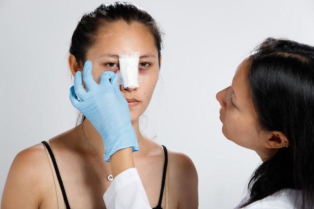 아시아 여성은 코 성형 수술을하여 형태를 높였습니다. 코 성형 후 의사는 2 주 동안 코 얼굴에 붕대를 감아 야합니다.