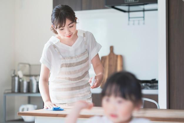 Азиатская женщина дезинфицирует домашний обеденный стол со спреем