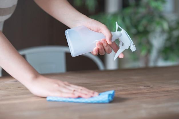 アジアの女性がスプレーで家のダイニングテーブルを消毒