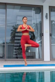 아시아 여자는 빨간 스포츠 착용에 수영장 여성으로 빌라 외부 요가 매트에 요가 포즈를
