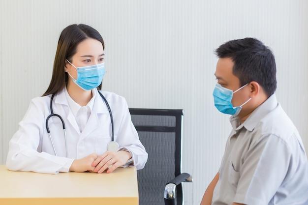아시아 여성 의사 환자에게 질문하기 의료에서 항상 외과용 마스크를 착용하여
