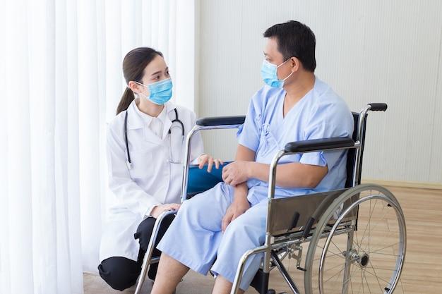 아시아 여성 의사는 휠체어에 앉아 있는 남성 환자와 함께 몇 가지 정보를 설명하고 제안합니다.