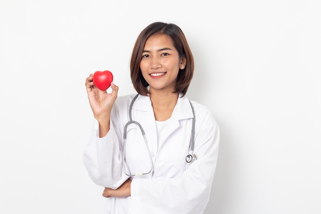 Asian woman doctor holding heart with stethoscope isolated