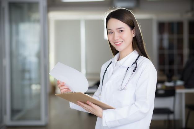 아시아 여성 의사는 병원에서 일하는 동안 클립보드를 손에 들고 미소를 짓고 있습니다.