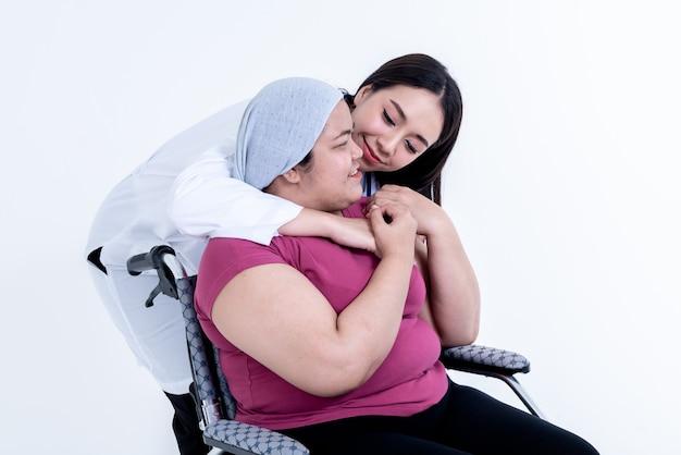 Азиатская женщина-врач обнимает пациентку, которая страдает ожирением и сидит в инвалидной коляске, чтобы поощрить ее