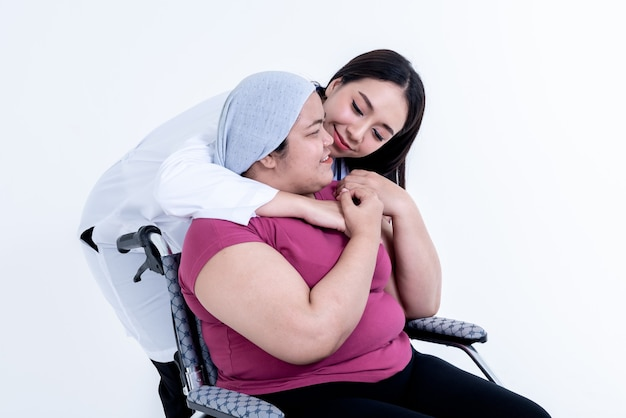 Asian  woman doctor hugging a woman patient to encourage, who is obese and sit in a wheelchair