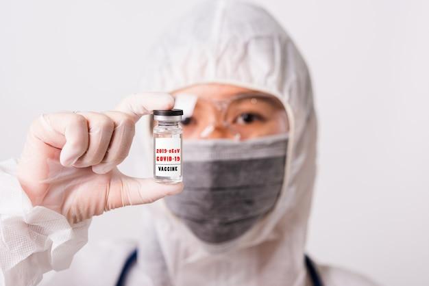 Ppeの制服を着たアジアの女性医師と薬瓶コロナウイルスワクチンボトルを保持している研究室で保護マスクを身に着けている手袋