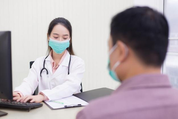 아시아 여성 의사는 병원에서 환자의 건강에 대해 이야기한 후 정보를 컴퓨터에 기록하기 위해 키보드로 타이핑을 하고 있습니다.